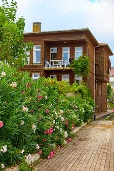 Uma velha casa de quatro andares com um jardim verde florido.