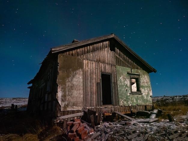 Uma velha casa em ruínas sob um céu estrelado.