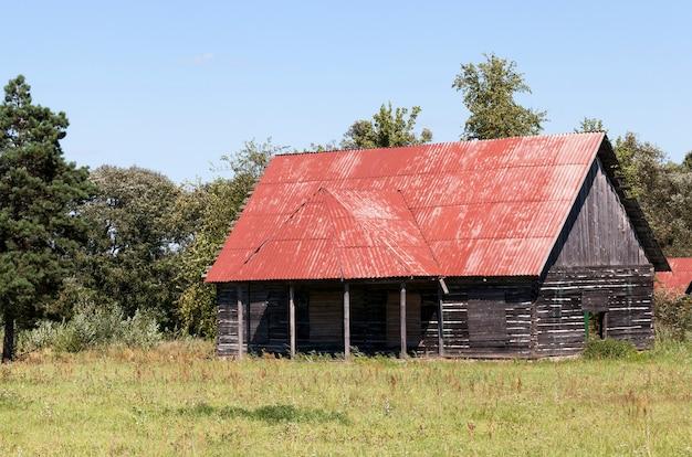 Uma velha casa inacabada abandonada de barras de madeira, localizada na mata, o telhado foi pintado com tinta