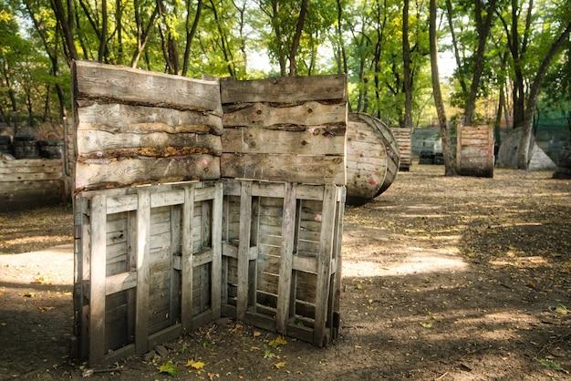 Uma velha cerca de madeira na base para um jogo de paintball, atrás da qual jogadores preocupados se escondem
