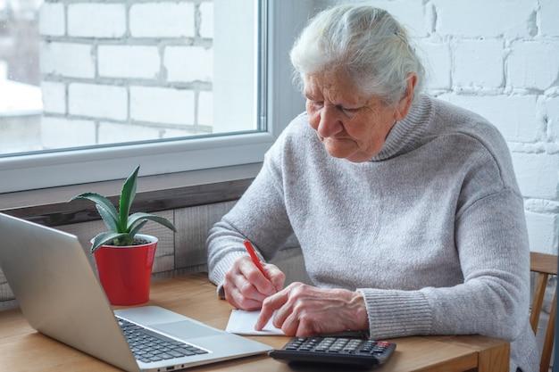 Uma velha está sentado à mesa na frente do laptop.