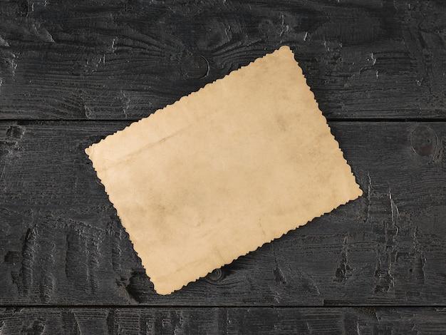 Uma velha foto de cabeça para baixo em uma mesa de madeira escura. o assunto dos valores familiares. a vista do topo. postura plana.