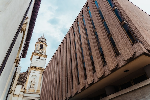 Uma velha igreja entalada entre as paredes de novas construções modernas.