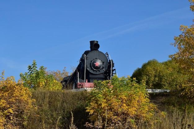 Uma velha locomotiva a vapor em funcionamento sai da estação da vila locomotiva a vapor em vista frontal com decoração de outono
