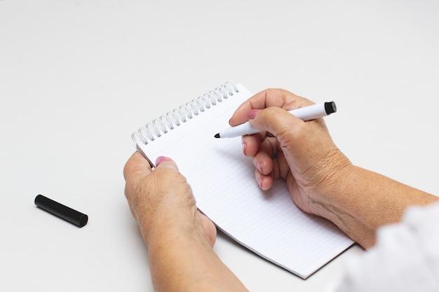 Uma velha mão enrugada segurando uma caneta