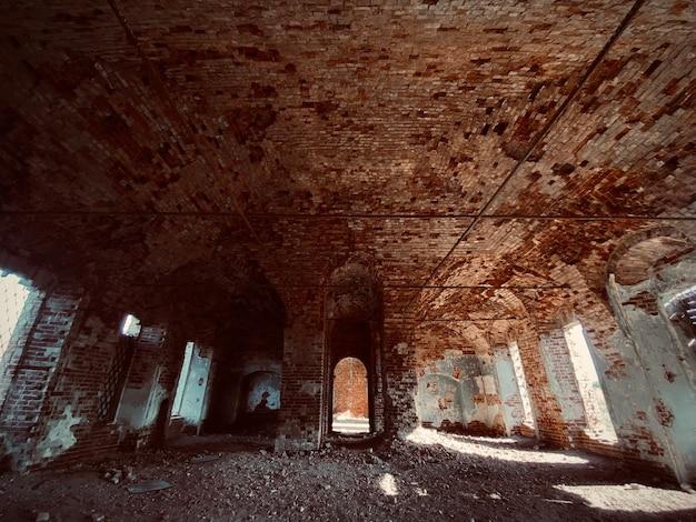 Uma velha parede de tijolos vermelhos em ruínas de uma igreja abandonada