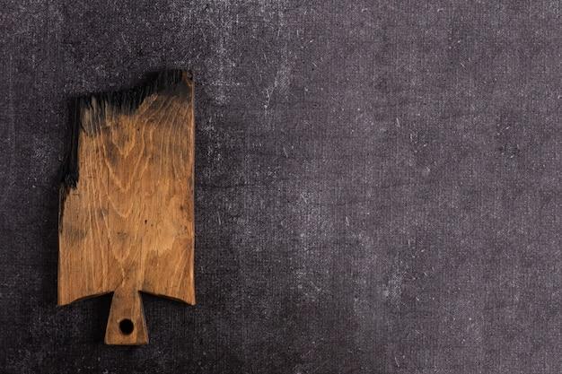 Uma velha placa de corte escura sobre um fundo escuro. a placa esta carbonizada