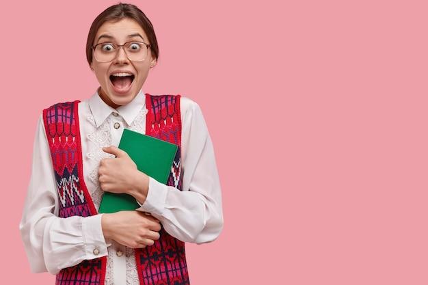 Uma velha professora da moda cheia de alegria parece maravilhada, usa grandes óculos quadrados e carrega um bloco de notas verde