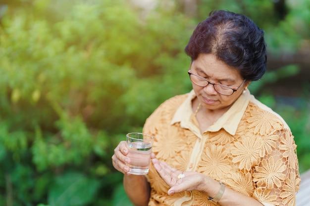 Uma velha tailandesa se senta e olha para o comprimido em sua mão com um copo d'água para comer