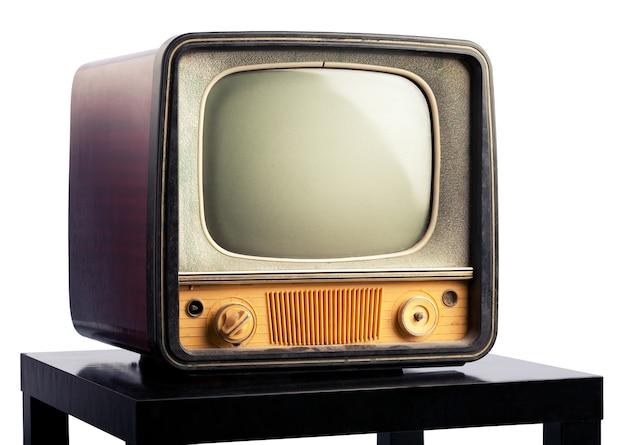 Uma velha televisão em pé sobre uma mesa preta sobre fundo branco