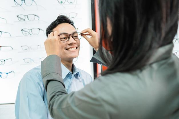 Uma vendedora coloca óculos em um cliente do sexo masculino enquanto está no oculista