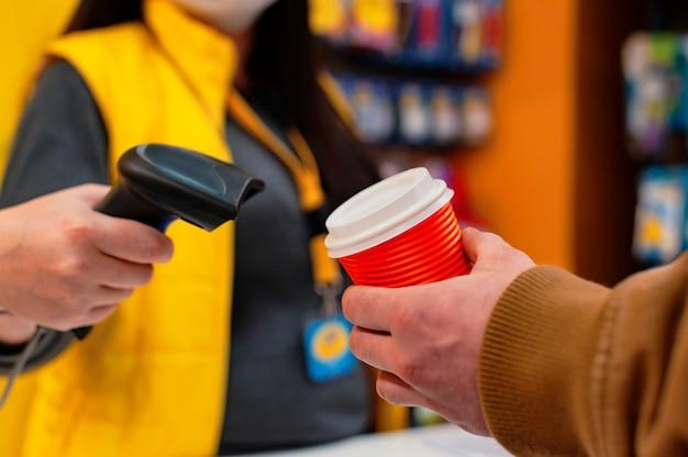Uma vendedora com uma máscara médica de um vírus segura um leitor de código de barras nas mãos um homem com um copo de café na mão paga no caixa