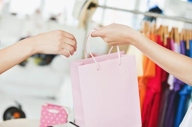 Uma vendedora dando uma sacola de compras a um cliente