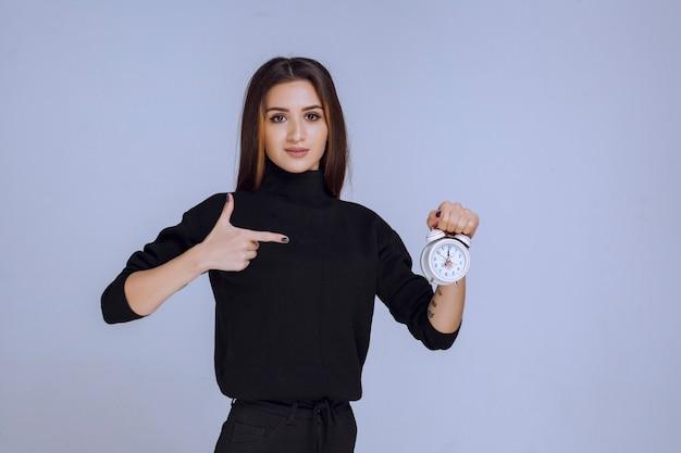 Uma vendedora segurando um despertador e promovendo-o.