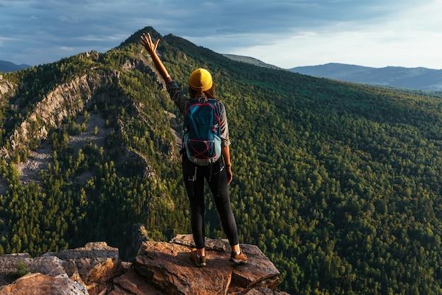 Uma viajante com uma mochila está parada na beira da montanha, uma vista traseira. uma jovem com uma mochila fica na beira de um penhasco e olha para o céu com a mão levantada. copie o espaço
