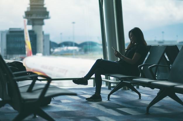 Uma viajante usando um telefone celular enquanto está sentada no aeroporto