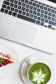 Uma visão aérea da baga cheesecake; matcha de chá verde e laptop na mesa branca