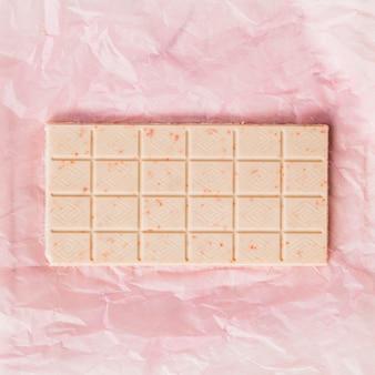 Uma visão aérea da barra de chocolate branco no envoltório de papel rosa