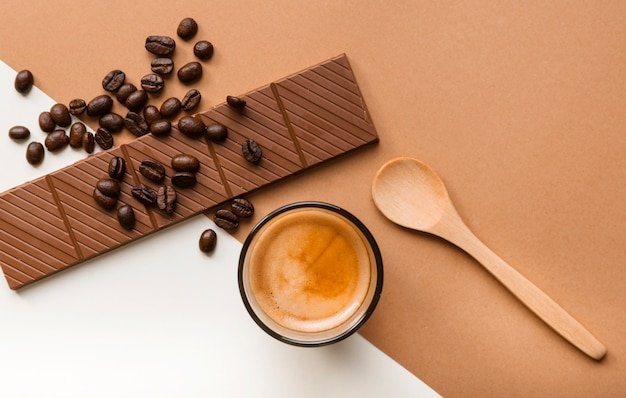 Uma visão aérea da barra de chocolate; grãos de café torrados com copo de café e colher