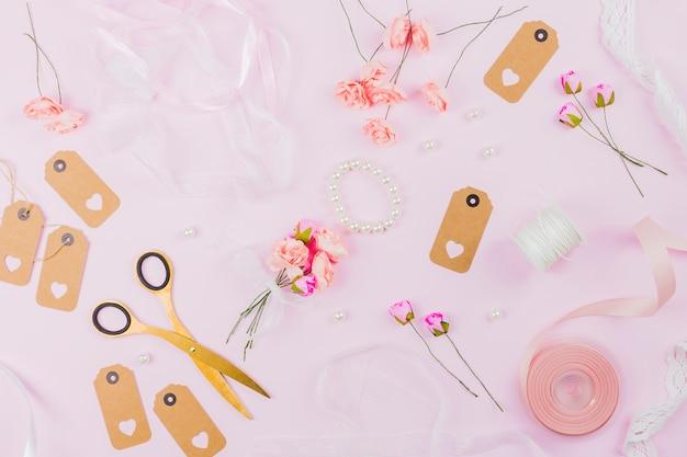 Uma visão aérea da fita; rosa artificial; pérolas; fita; tag e tesoura em fundo rosa