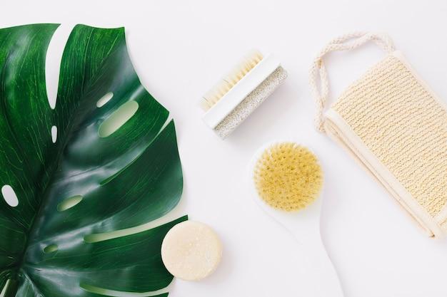 Uma visão aérea da folha de monstera com bucha; sabonete; escova e pedra-pomes escova de pedra sobre o pano de fundo branco