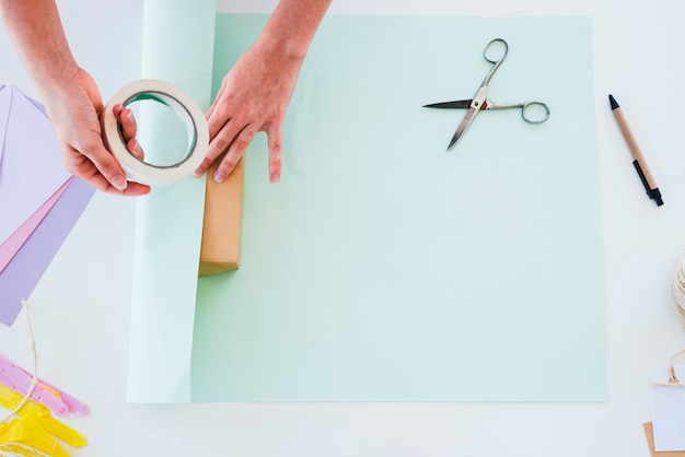 Uma visão aérea da mão da mulher, furando o papel na caixa de presente sobre a mesa branca