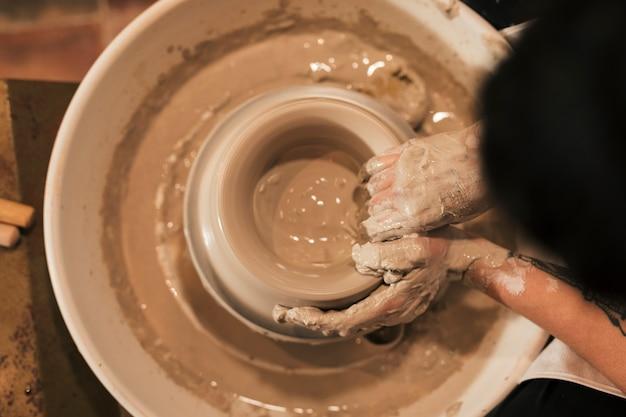 Uma visão aérea da mão do oleiro feminino, criando um pote de barro na roda de oleiro