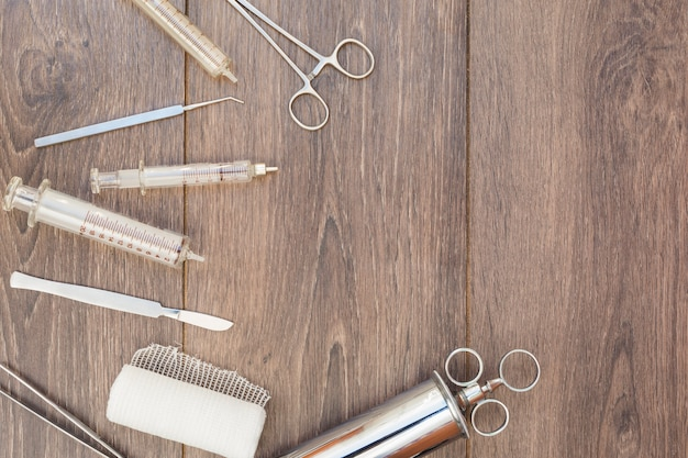 Uma visão aérea da seringa de aço inoxidável vintage; otoscópio e equipamentos médicos na mesa de madeira
