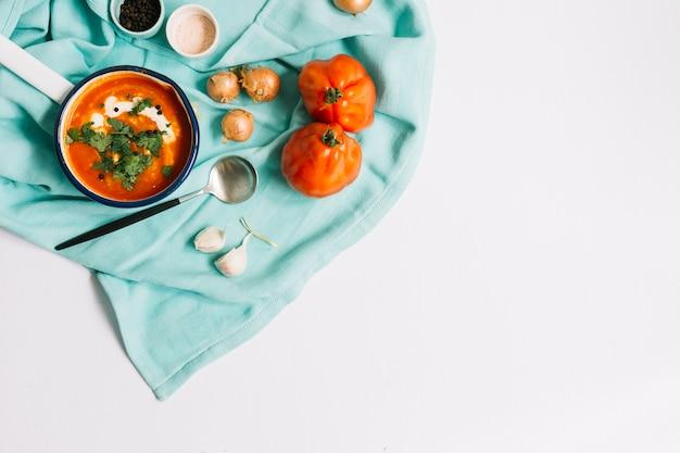 Uma visão aérea da sopa de tomate com ingredientes na toalha de mesa azul contra um fundo branco