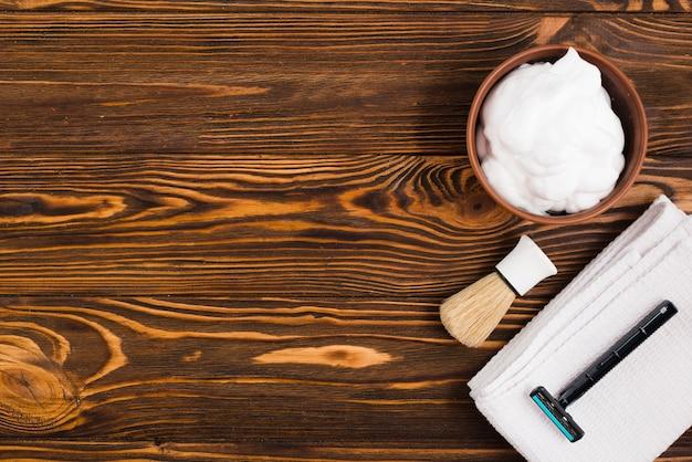 Uma visão aérea da tigela de espuma; escova de barba; navalha e guardanapo branco dobrado contra o pano de fundo texturizado de madeira