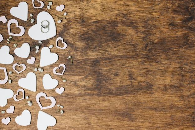 Uma visão aérea de alianças de prata em forma de coração sobre o cenário de madeira