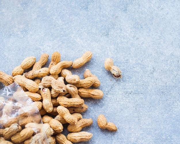 Uma visão aérea de amendoins com casca no plano de fundo texturizado áspero