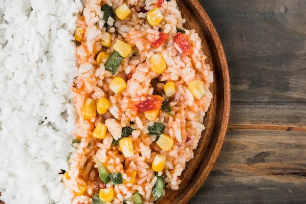 Uma visão aérea de arroz branco cozido e arroz frito chinês com legumes na bandeja de madeira