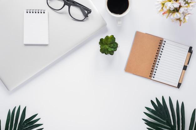 Uma visão aérea de artigos de papelaria do escritório com laptop; xícara de café; vaso de flor e folhas no pano de fundo branco