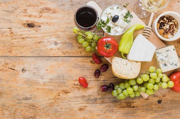 Uma visão aérea de blocos de queijo com uvas; tomates; pimenta verde e frutas secas