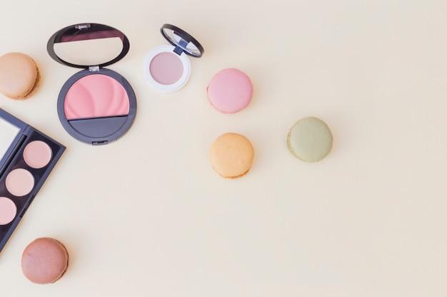 Uma visão aérea de blush e sombra com macaroons em fundo colorido