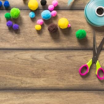 Uma visão aérea de bola de algodão colorido; fita e tesoura na prancha de madeira