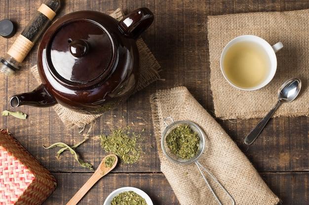 Uma visão aérea de bule marrom; xícara de chá de ervas e folhas de chá secas na mesa de madeira