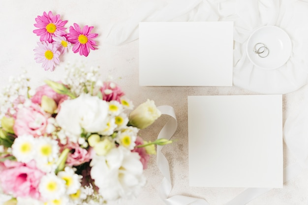 Uma visão aérea de buquês de casamento com cartão branco e anéis em pano de fundo concreto