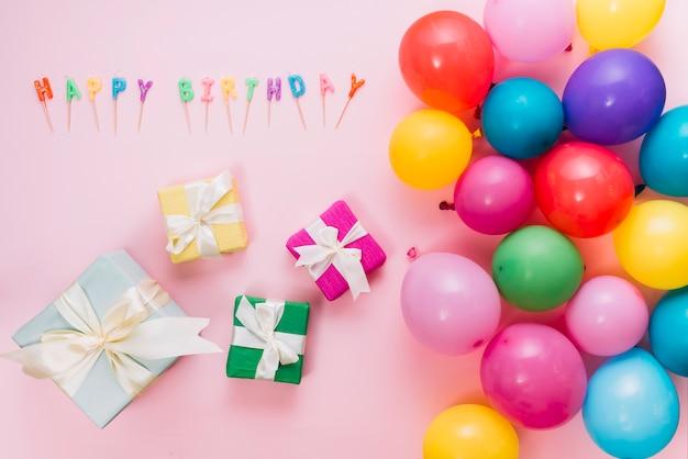 Uma visão aérea de caixas de presente coloridas; balões e velas de feliz aniversário no pano de fundo rosa
