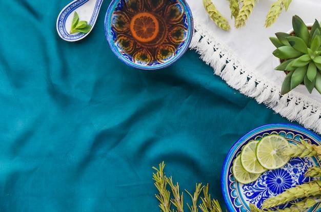 Uma visão aérea de chá de ervas limão com ingredientes na toalha de mesa