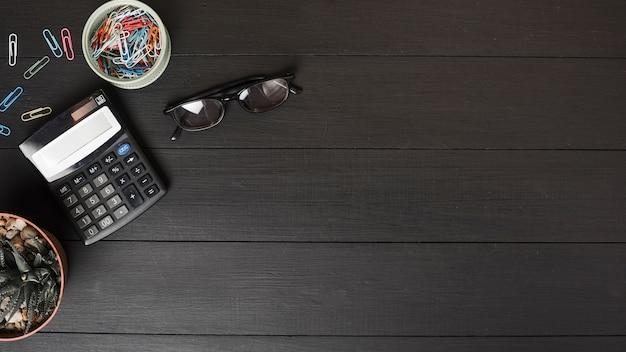 Uma visão aérea de clipes de papel coloridos; calculadora e óculos na mesa de madeira preta