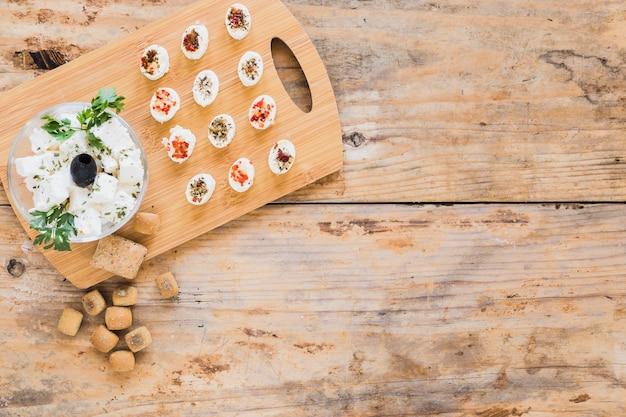 Uma visão aérea de cubos de queijo na tábua de madeira