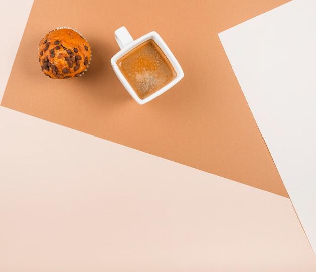 Uma visão aérea de cup cakes e xícara de café no pano de fundo duplo bege