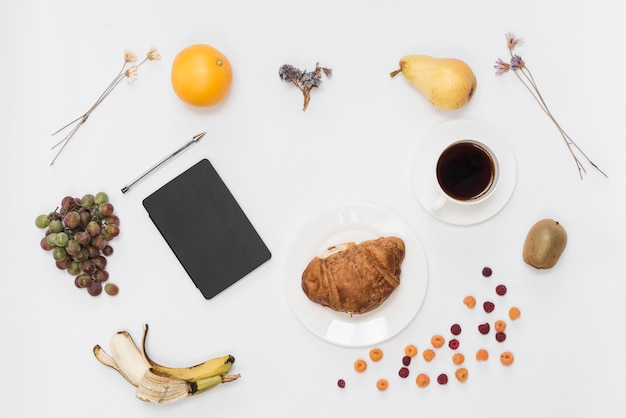 Uma visão aérea de diário e caneta com frutas; café e croissant isolado no fundo branco