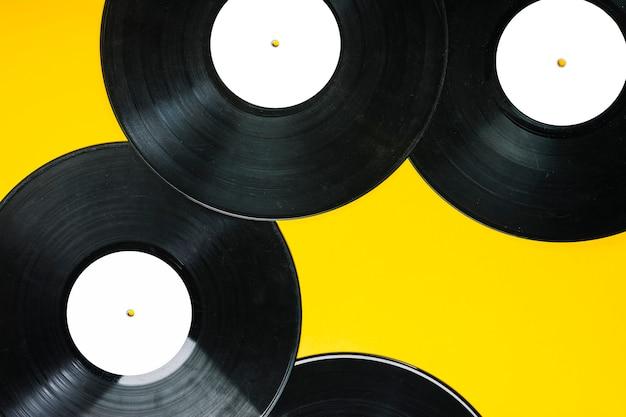Uma visão aérea de discos de vinil em fundo amarelo