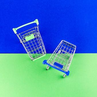 Uma visão aérea de dois carrinhos de compras em fundo azul e verde