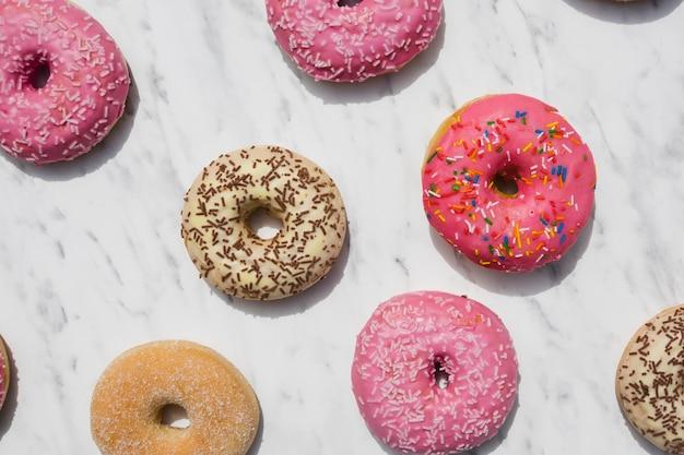 Uma visão aérea de donuts coloridos em pano de fundo texturizado em mármore