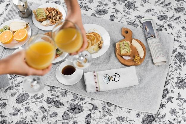 Uma visão aérea de duas pessoas brindando copos de suco durante o café da manhã