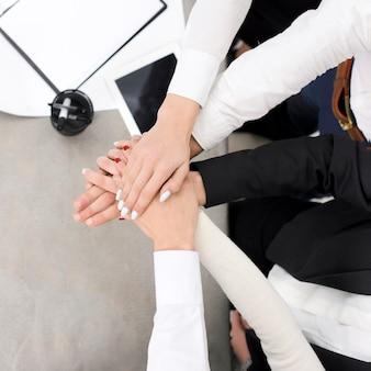 Uma visão aérea de empresários empilhando a mão do outro sobre a mesa